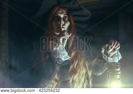 Scary redhead witch with a lantern near the wooden house. Magic, dark force, spell. Halloween.