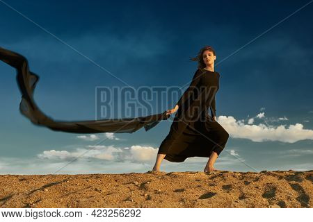 Beautiful romantic girl in a long black dress posing in the desert with a scarf fluttering in the wind. Sky background. Feeling of flight, dreams.