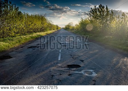 Poor Quality Road With Potholes. Holes In The Roadway. Risk Of Driving.