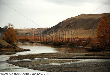 The Winding River Spilled Into A Narrow Autumn Valley Surrounded By Hills.