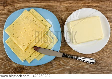 Few Thin Slices Of Cheese In Light-blue Glass Plate, Table Knife, Piece Of Butter In White Plate On