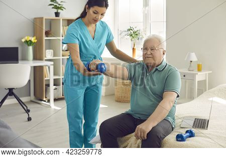Physical Therapist Nurse Helping Patient To Exercise With Dumbbells At Home
