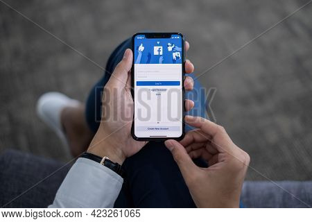 Chiang Mai Thailand. June 10, 2021. A Man Holds Iphone With Facebook Application On The Screen. Face