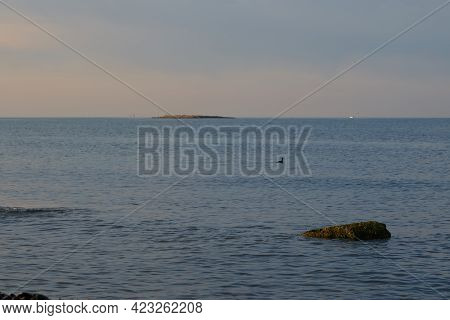 The Sunrise Over The Calm Sea Casts Rays Of Orange Light Into The Air As The Setting Sun Penetrates