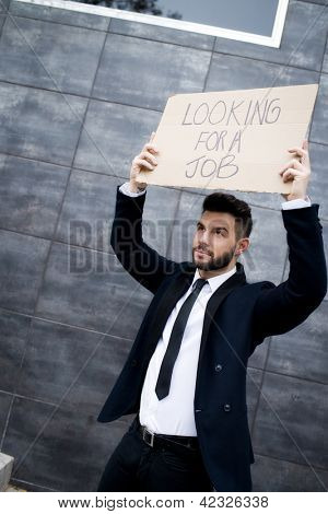 Young business woman holding sign Looking for a job