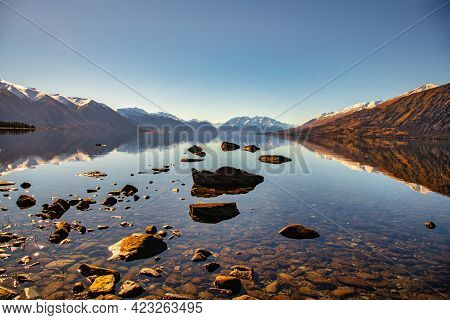 Rocky Shore Of Lake Ohau With The Snow Capped Southern Alps Reflected In The Calm Water