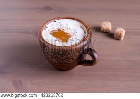 Close-up Of Hot Coffee With Milk In A Fired Earthenware Mug With Cane Sugar Pieces. Natural Wood Bac