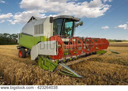 Modern Combine, Harvester, Harvesting On Wheat Field, Cloudy Sky