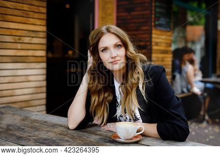 Young Business Woman Drinking Cappuccino And Cup Of Coffee. Happy Alone Woman In Outdoor Cafe Or Res