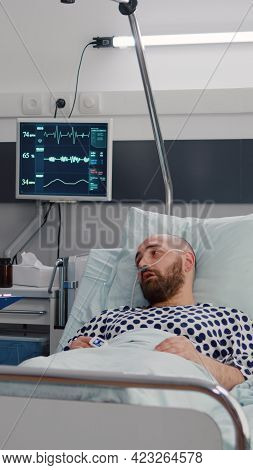 Medical Nurse Discussing Illness Treatment With Hospitalized Sick Man Resting In Bed During Rehabili