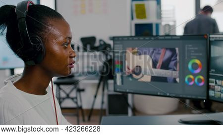 Beautiful African Woman Videographer With Headphones Editing Video Footage On Pc With Two Displays W