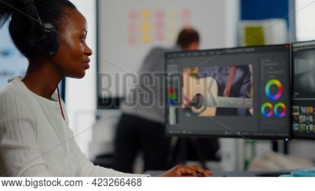 African Video Editor With Headset Listening Music Wihile Editing Footage And Sound Sitting In Creati