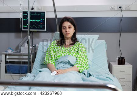 Sick Woman Looking Into Camera Lying In Bed Recovering After Respiratory Surgery. Patient With Breat