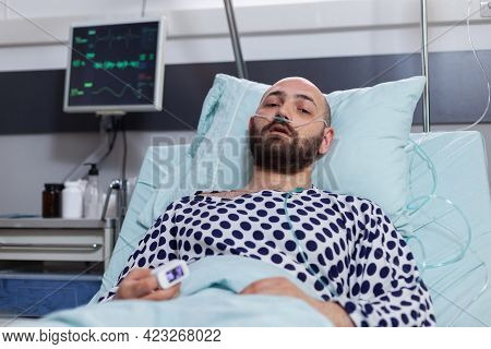 Potrait Of Sick Man Wearing Nasal Oxygen Tube Having Respiratory Disease Lying In Bed During Recover