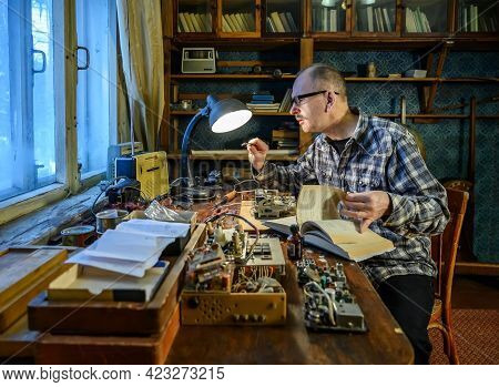 Radio Amateur Engaged In The Repair Of A Radio Receiver. On The Table Are Radio Parts And Tools