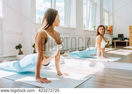 Young Female Do Complex Of Stretching Yoga Exercises On Floor In Light Sunny Room In Front Of Mirror