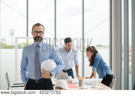 Construction Engineer Manager Stand And Holding White Hardhat In Front Of Engineers Team Meeting For