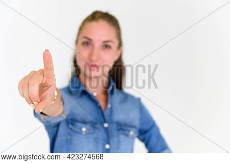 Portrait Of Beautiful Woman In Blue Jeans Shirt Pointing Her Finger And Looking At Camera On White B