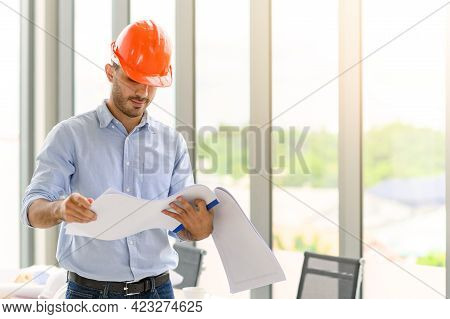 Portrait Of Construction Engineer Manager Workers In Orange Hardhat And Looking Layout Plan. Posing