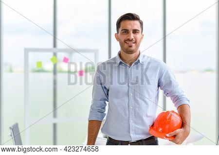 Portrait Of Construction Engineer Manager Holding Orange Hardhat. Posing Standing In Office. Copy Sp