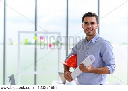 Portrait Of Construction Engineer Manager Holding Orange Hardhat And Blueprint. Posing Standing In O