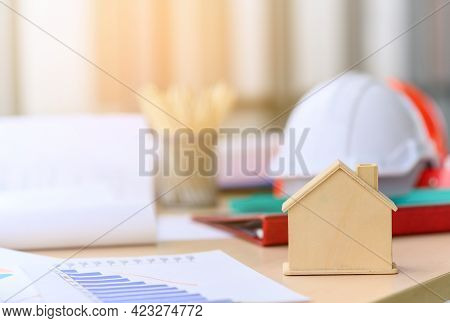 Small Wooden House Or Home With Engineering Tools, Blueprint And White Safety Helmet On Messy Table,