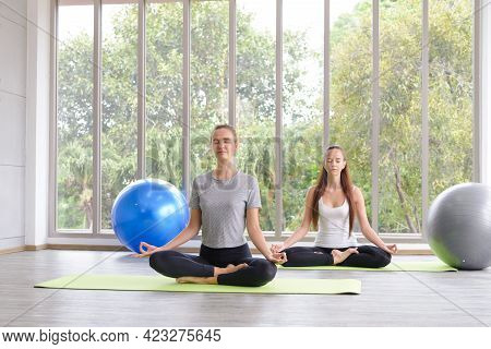 Time For Practicing Yoga. Two Youngs Attractive Women Sitting In Ardha Padmasana Exercise, Lotus Pos