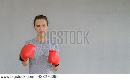 Portrait Of Young Fitness Sporty Woman In Sportswear With Red Boxing Gloves Looking At The Camera On