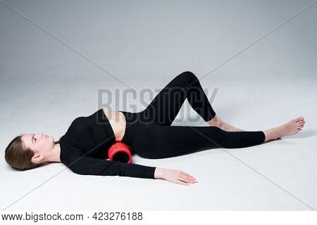Girl Fitness Trainer In A Black Top And Leggings Lies On The Floor And Does Exercise Using The Fasci