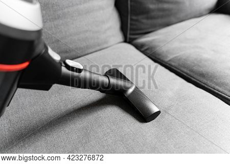 Cleaning Grey Sofa With Wireless Vacuum Cleaner. Handheld Cordless Cleaner. Household Appliance. Hou