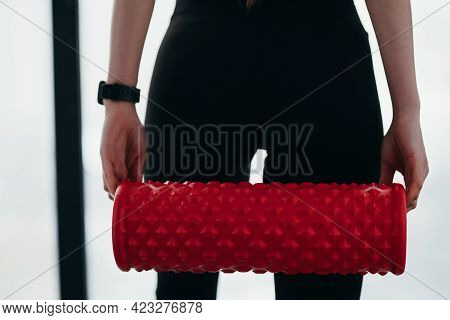 Photo Close-up And Behind. A Girl In Black Leggings Holds A Fascia In Her Hands While Standing Again