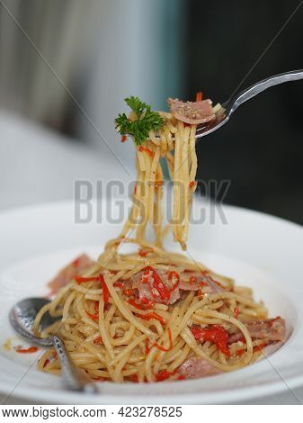 Fork Scooping Spaghetti With Spicy Ham In White Plate, Food