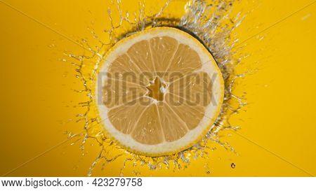 Fresh lemon slice falling into splashing water splashing
