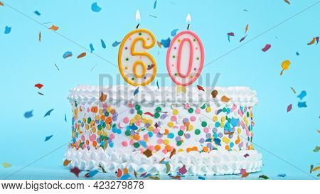 Colorful tasty birthday cake with candles shaped like the number 60.