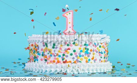 Colorful tasty birthday cake with candles shaped like the number 1.