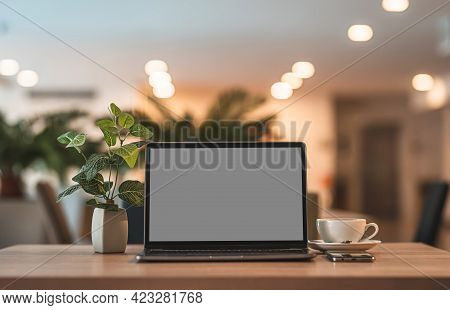 Mockup Of Laptop Computer With Empty Screen With Coffee Cup And Smartphone On Table Of The Coffee Sh