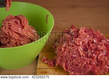 Steel meat grinder processing meat, cooking meat on wooden table