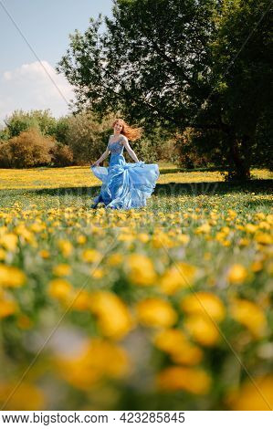 A Happy Fairy-tale Girl In An Airy Blue Dress Runs Joyfully Along The Green Lawn In The Park. Bloomi