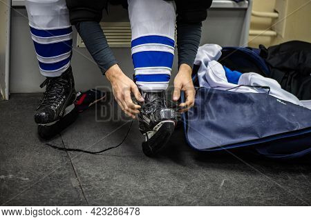 Ice Hockey Players Play Ice Hockey. Hockey Player Tying Shoelaces On Skates
