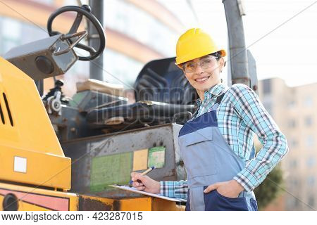 Portrait Of Smiling Female Foreman In Helmet With Documents And Pen On Background Of Asphalt Paver