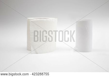 A New Roll Of Toilet Paper And And Empty Toilet Paper Rolls On White Background.