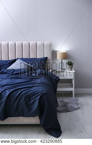 Bed With Stylish Silky Linens In Room