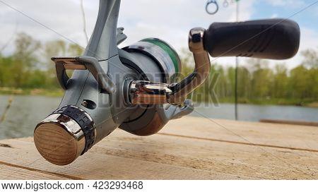 Carp Fishing Rod Isolated On The Lake And Wooden Bridge. Carp Feeder Spinning Reel Close Up. Fishing