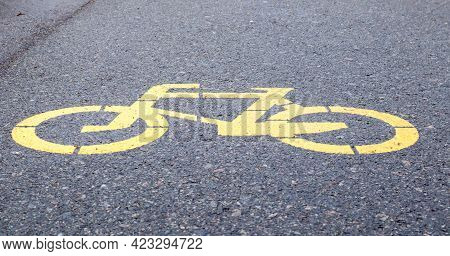 Bicycle Symbol Representing A Path For Bicycles. Yellow Painted Sign For Bicycles On The Asphalt. Fl