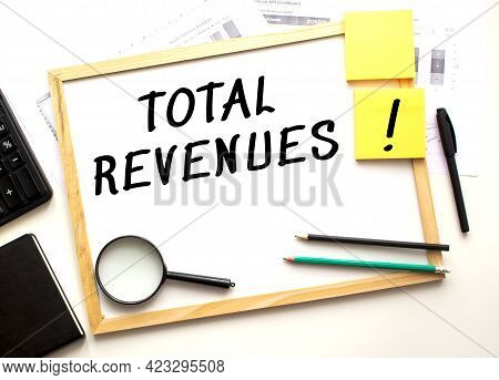 Total Revenues Text Is Written On A White Office Board. Work Table With Office Supplies. Business An