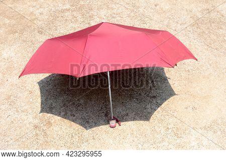 Uv Umbrella In The Summer Sun. Red Color Beach Umbrella Blocking The Sunlight. Shadow On The Sandy F