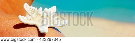closeup of a white starfish on the shoulder of a suntanned man on the beach, with the sea and a ship in the background, in a panoramic format to use as web banner or header