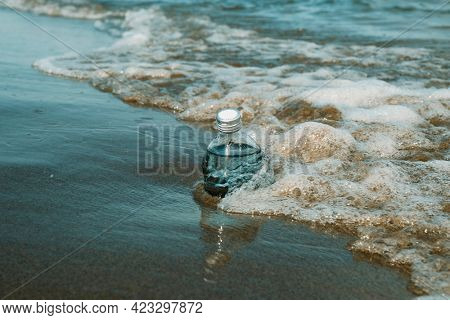 a glass reusable water bottle on the seashore of a lonely beach, next to a foamy wave