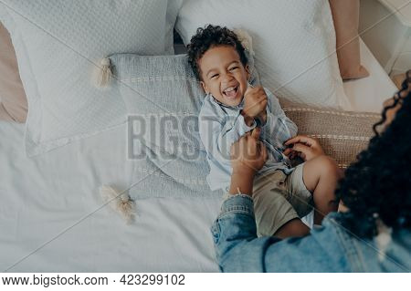 Sweet Little Boy Kid Laughing Loudly And Smiling While His Loving Mom Tickling Him On Bed With Lot O