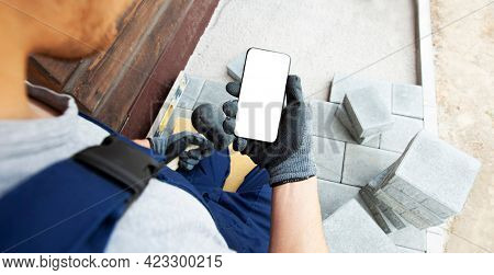 bricklayer holding the phone with blank screen in hand on gloves.  mockup for house repair or building